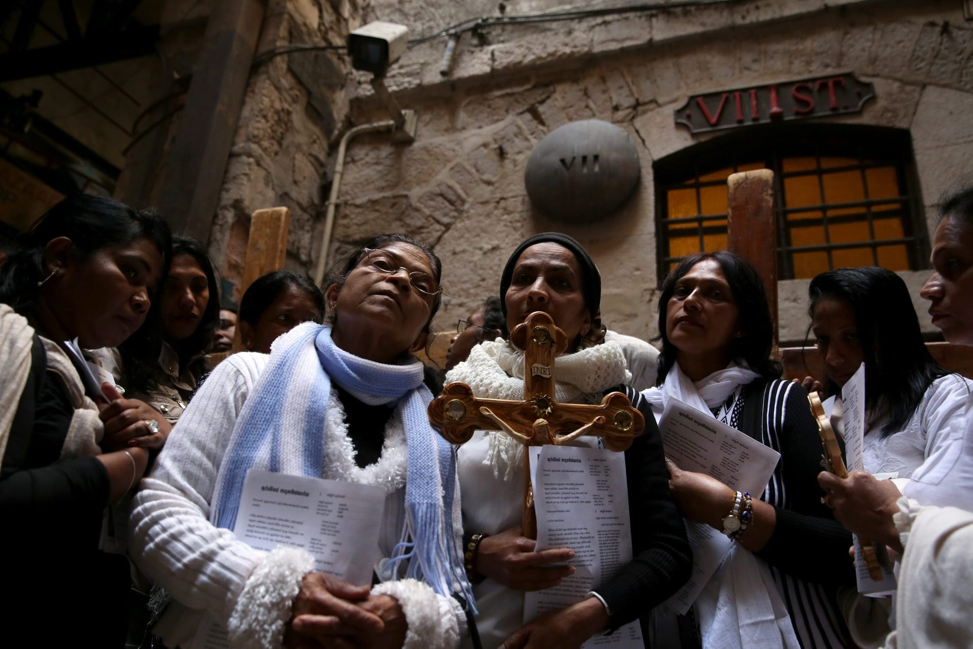 Catholic pilgrims from Sri Lanka carry a wooden cross along the Via Dolorosa (Way of Suffering) as they pray at the 7th station  in Jerusalem's Old City during the Good Friday procession on March 25, 2016.