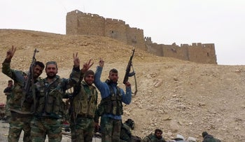 Syrian pro-government forces gesture next to the Palmyra citadel on March 26, 2016.