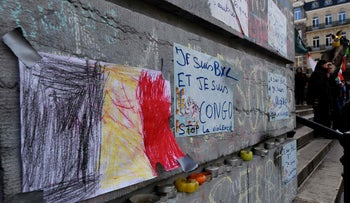 """Belgium's flag drawn on a piece of paper next to a message reading, """"I am Brussels and I am Congo, stop violence"""" at the makeshift memorial outside the stock exchange in Brussels, March 27, 2016."""