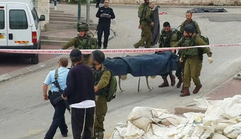 A screenshot from a video showing the soldier shaking hands with far-right activist Baruch Marzel (front) at the scene of a stabbing attack in Hebron on March 24, 2016.