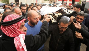 Mourners carry the body of Ramzi al-Qasrawi, 21, a Palestinian man who was killed during a stabbing attack in Hebron, March 26, 2016.