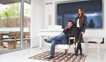 Gilbert Chikli, 50, and his wife Shirly Chikli, 31, pose for a photo at their home in Ashdod, Israel, March 28, 2016.