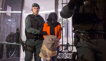 A Spanish Civil Guard policeman escorts a detained woman while leaving an Industrial and Commercial Bank of China branch in Madrid, Spain, February 17, 2016.