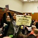Students hold up protest signs at the end of a public comment period during a University of California Board of Regents meeting, San Francisco, U.S., March 23, 2016.