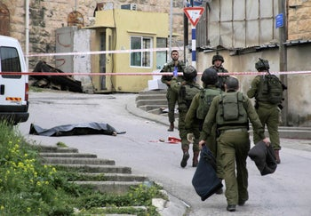 Israeli soldiers stand near the body of a Palestinian who was shot and killed by a soldier while laying wounded on the ground after a stabbing attack, Hebron, West Bank, March 24, 2016.
