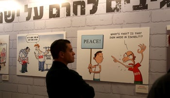 People look at caricatures of Israeli artists against the BDS movement displayed during the Ynet and Yedioth Ahronoth's anti-BDS conference, Jerusalem, Israel, March 28, 2016.