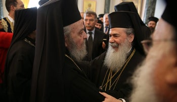 Greek Orthodox Patriarch of Jerusalem Theophilos III (right) is greeted by the former ousted Patriarch of Jerusalem, monk Irenaios, March 22, 2016.