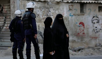 Women walk past by riot police watching for protesters, to prevent a third day of gathering of demonstrators against Saudi Arabia's execution of Shiite cleric Sheikh Nimr al-Nimr, Monday, Jan. 4, 2016.