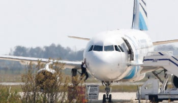 A man climbs out of the cockpit window an EgyptAir Airbus A-320 parked at the tarmac of Larnaca airport after being hijacked and diverted to Cyprus on March 29, 2016.