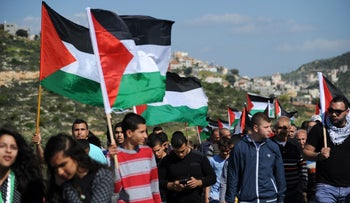Residents of Arabeh mark Land Day by marching and waving Palestinian flags, March 2014.