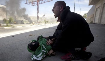 A Palestinian youth hovers over a teen killed at a 2014 protest in Beituniya