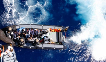 A photo from March 29 shows rescued migrants sit in a German Navy boat in the Mediterranean Sea off the coast of Libya.
