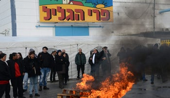 Workers at Pri Hagalil factory in Hatzor Haglilit protesting dismissal plans, Jan. 2015. Wooden pallets burn in what appears to be a parking lot as a couple of dozen workers look on.