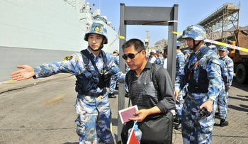 "Chinese navy soldiers gesture to Chinese citizens boarding the naval ship ""Linyi"" at a port in Aden, Yemen, March 29, 2015."