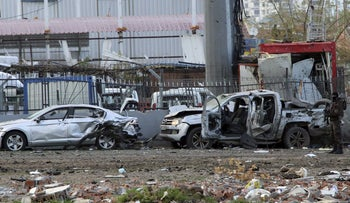 A member of the police special forces stands next to vehicles which were damaged by a car bomb attack in the Kurdish-dominated southeastern city of Diyarbakir, Turkey March 31, 2016.