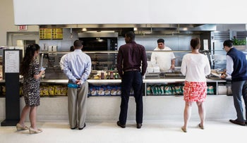 Employees wait in line for lunch at the Goldman Sachs Group cafeteria in New York, September 10, 2015.