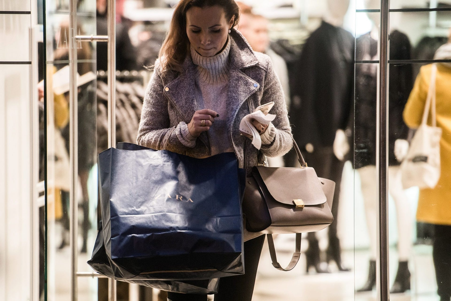 A shopper carries a branded shopping bag as she exits a Zara fashion store, operated by Inditex SA, in Budapest, Hungary, Dec. 5, 2015.