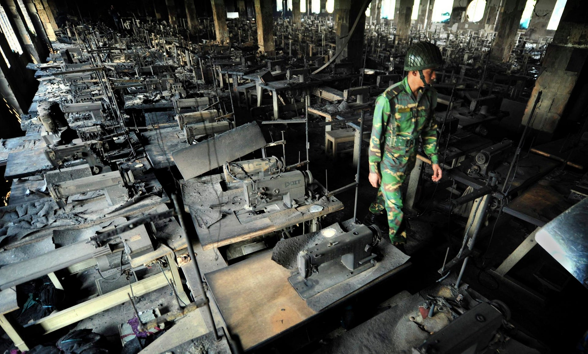 A police officer walks past rows of burnt sewing machines in the burned out Tazreen garment factory in Savar, on the outskirts of Dhaka, Bangladesh, November 25, 2012.