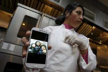 Dhuha Jasim, a refugee from Iraq, shows a picture of her family who lives in Iraq, at Eat Offbeat, a New York food company where refugees make and deliver ethnic fare, in their kitchen area in the Queens borough of New York February 25, 2016.