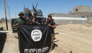 Iraqi security forces stand with an Islamic State flag which they pulled down in the town of Heet in Anbar province, April 2, 2016