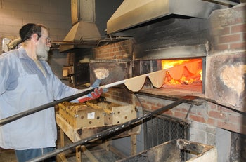 It takes about 20 seconds in a 1,300-degree, coal-and-wood-fired oven to bake shmurah matzah to perfection.