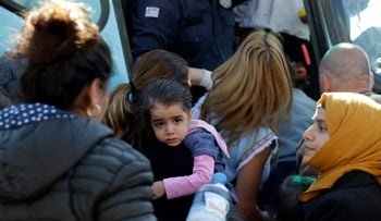Syrian families embark a bus, transferring them to the western coastal Greek town of Kyllini, from the Athens port of Piraeus, Greece, March 31, 2016.