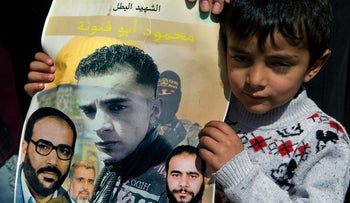 Suleiman Abu Fanuneh, 4, holds a poster with a picture of his brother, Mahmoud Abu Fanuneh, center, surrounded by photos of top Islamic Jihad officials, during his funeral in Hebron, March 19, 2016.