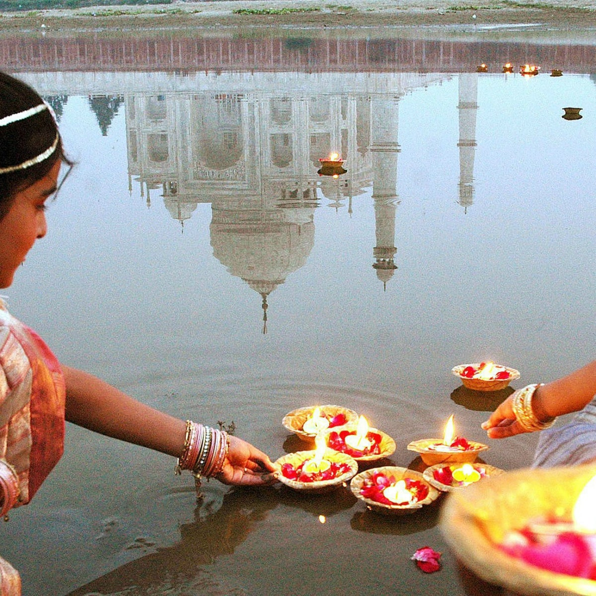 Indian teenagers place oil lamps onto the Yamuna River behind the Taj Mahal.