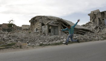 A boy runs near damaged buildings while competing in 'Freedom Marathon' marking the fifth anniversary of the Syrian crisis, in the town of Marat Numan in Idlib province, Syria, March 23, 2016.