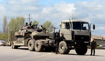 An Azeri military armored personnel carrier is seen on the bed of a truck in the town of Terter, Azerbaijan, April 4, 2016.