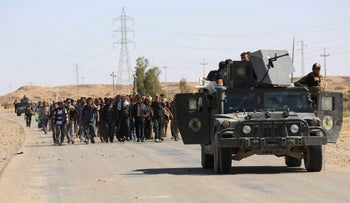 Iraq's elite counter terrorism troops escort people fleeing their homes during clashes between Iraqi security forces and Islamic State group militants in Hit, April 4, 2016.