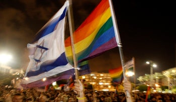 Israelis wave rainbow flags as they attend a rally in Tel Aviv August 8, 2009.