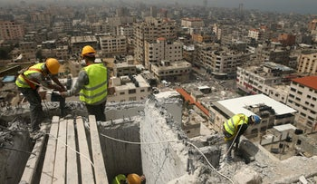 Palestinian workers removing debris from buildings which were destroyed during the 50-day war between Israel and Hamas militants in the summer of 2014, in Gaza City, on April 5, 2016.