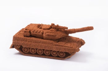 "A sand-covered miniature tank by artist Farid Abu Shakra, part of his ""sand games"" series."