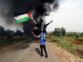 Palestinian protesters wave a flag during clashes with Israeli troops in the West Bank village of Duma near Nablus, April 5, 2016.