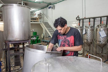 Itai Gutman at work at the Herzl Brewery in Jerusalem. His arm features a tattoo of the earliest-known recipe for beer.