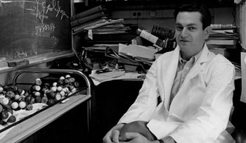 Marshall Warren Nirenberg, biochemist and geneticist, discovered how DNA is translated to RNA which is translated to protein. Shown in 1962, on the backdrop of a disorderly bookcase behind him and a blackboard to his right (as he sits facing the camera, wearing a white lab coat and clasping his knees.)