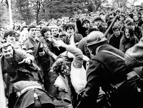 A stick-swinging Madison riot police officer beats back an angry throng of University of Wisconsin protesters, October 19, 1967 on campus.