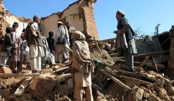 Afghans sift through the rubble of houses destroyed by an earthquake in Sherzad district of Nangarhar province, April 17, 2009.