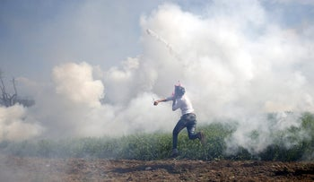 A migrant throws back a teargas canister at Macedonian police during clashes at the Greek-Macedonian border near the makeshift Idomeni camp, Greece, April 10, 2016.