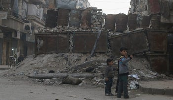 Children play near barricades in a street in Aleppo's rebel-controlled Bustan al-Qasr neighborhood, April 6, 2016.