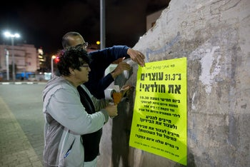 Sheffi Paz sticking posters around the Shapira neighborhood in south Tel Aviv