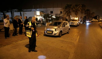 The scene of the hit-and-run accident in Ashdod, April 10, 2016. A police official shines a flashlight on a spot on the road.