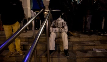 An asylum seeker sits outside of the visa renewal center at the government complex in Tel Aviv, December 31, 2013.