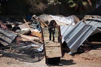 A woman from the Arab Jahalin Bedouin community carries a mirror after the demolition of her home in the West Bank Bedouin camp of al-Khan al-Ahmar on April 7, 2016.