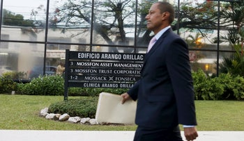 A lawyer from the Mossack Fonseca law firm walks past a sign with a list of companies including Mossack Fonseca at the Arango Orillac Building in Panama City, April 11, 2016.