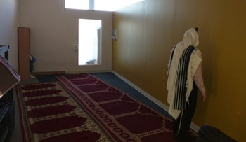 A Jewish man draped in a tallit prays in a mosque at JFK airport, New York, April 2016.