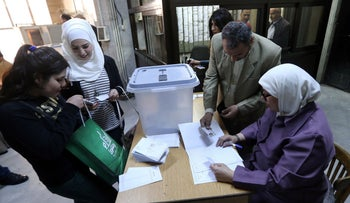 Syrians register to cast their votes at a polling station during parliamentary elections, Damascus, Syria, April 13, 2016.