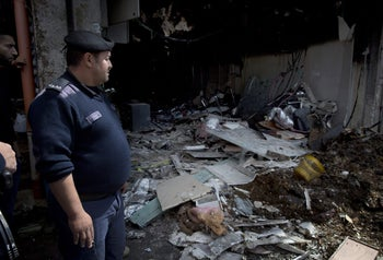 Palestinian police officers secure the parameter of torched shops in a commercial building at the main market of the West Bank city of Ramallah, Thursday, April 14, 2016.