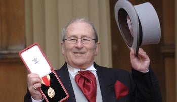British playwright Arnold Wesker poses at Buckingham Palace after being knighted, London, U.K., February 22, 2006.